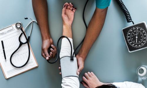 Ärztin misst Blutdruck bei einem männlichen Patienten