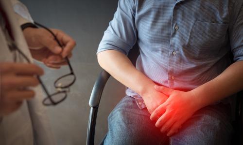 Mann mit seinen Händen im Schritt sitzt beim Arzt