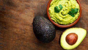 Avocado, Schale mit Guacamole, 2 Avocados auf Tisch