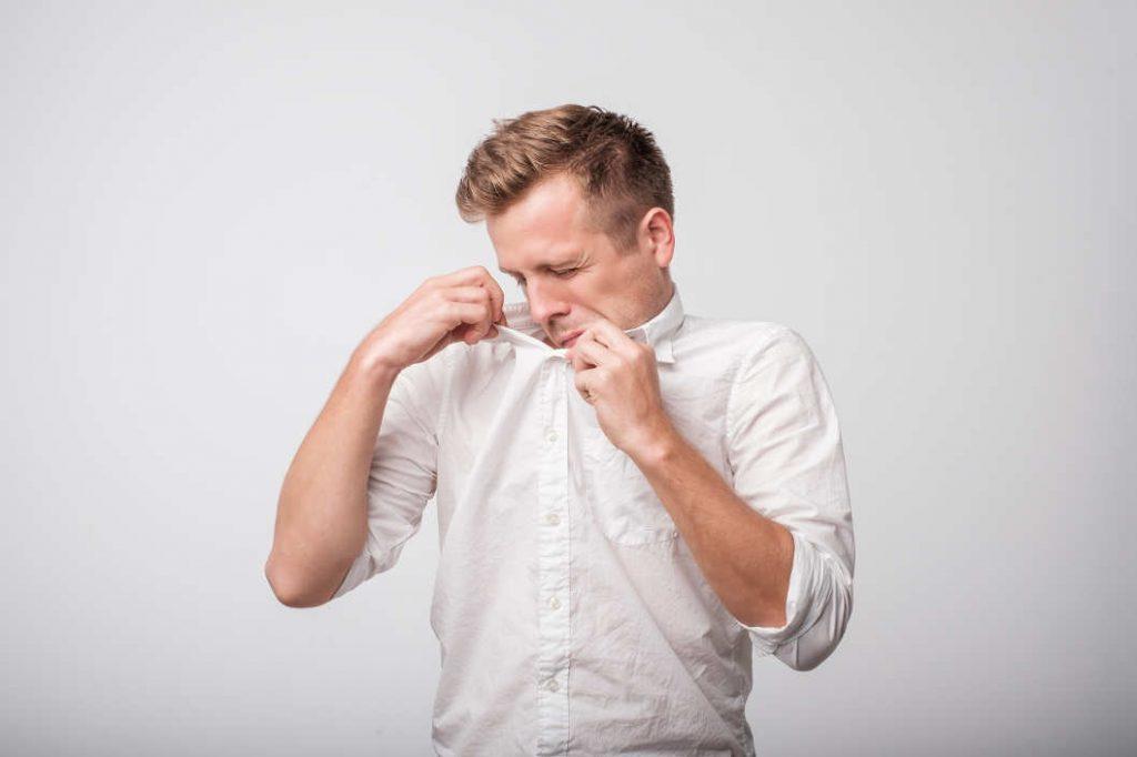 Schwitzender Mann riecht an seinem Hemd wegen Schwitzen
