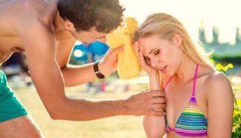Sonnenstich Gefahr Mann hält Kühlakku Frau