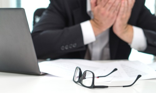 Mann im Anzug sitzt im Büro Brille Hände vor dem Gesicht