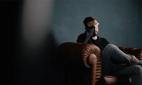hirndruck, Mann sitzt auf Sofa stützt Kopf auf Hand