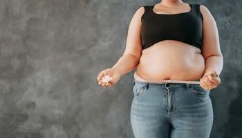 Adipositas Anzeichen Kräftigere Frau Maßband um Bauch