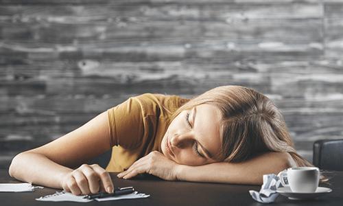 Boreout Auwirkungen Frau schläft Arbeitsplatz