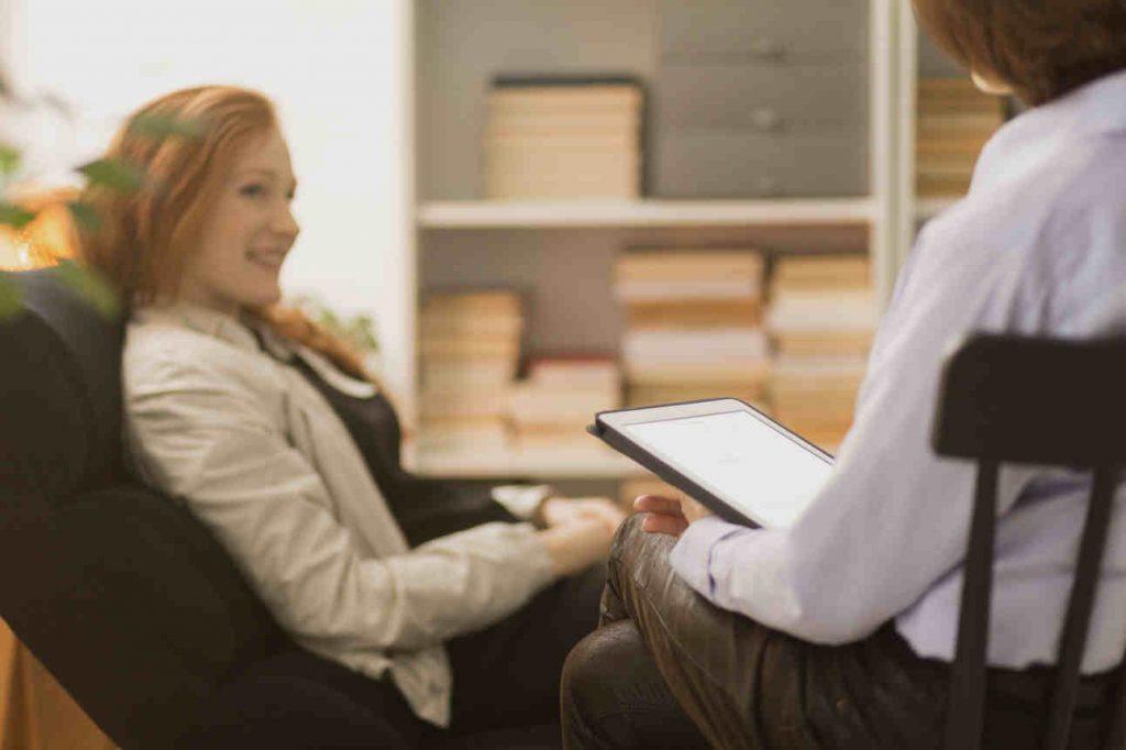 Junge Frau sitzt bei Therapeutin