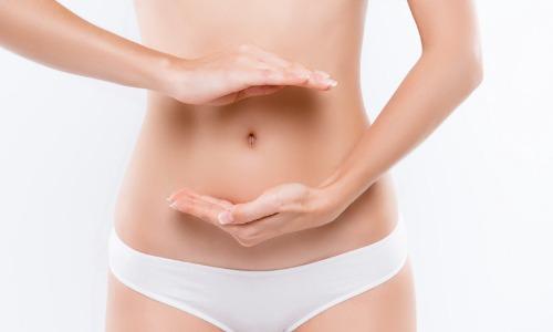 Frau hält Hände vor Bauch Darmflora