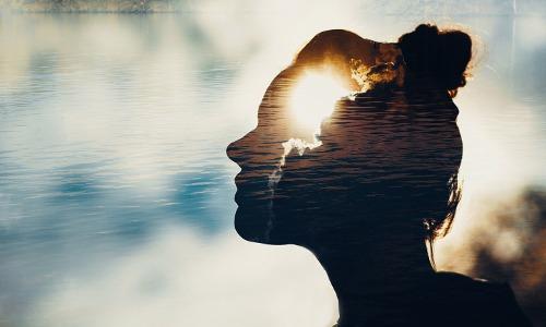 Durchscheinender Frauenkopf im Profil vor bewölktem Himmel