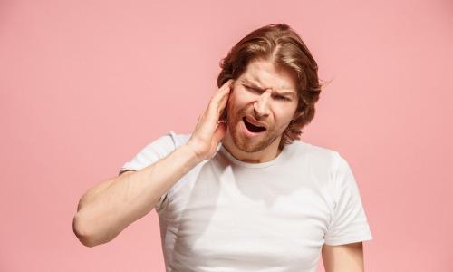 Mann mit Hörsturz Symptomen hält Hand an Ohr