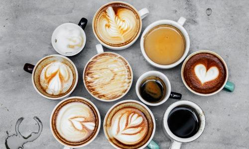 Mehrere Tassen Cappuccino und Espresso stehen auf einer Tischplatte