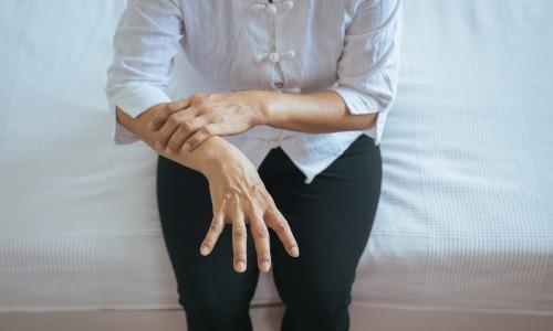 Frau sitzt auf Bettkante und hält ihren Unterarm