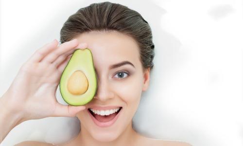 Frau liegt auf weißer Unterlage, lacht und hält halbierte Avocado vor ihr Gesicht
