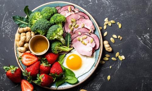 Teller mit Obst, Gemüse und tierischen Produkten steht auf einer dunklen Platte