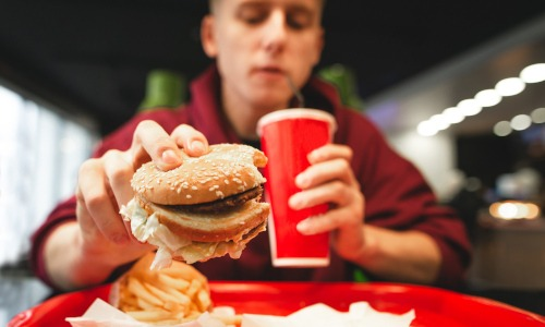 männlicher Teenager hält einen Hamburger und einen roten Becher