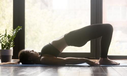Frau liegt am Boden und macht eine Schulterbrücke