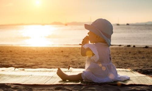 Baby sitzt am Strand bei Sonnenuntergang