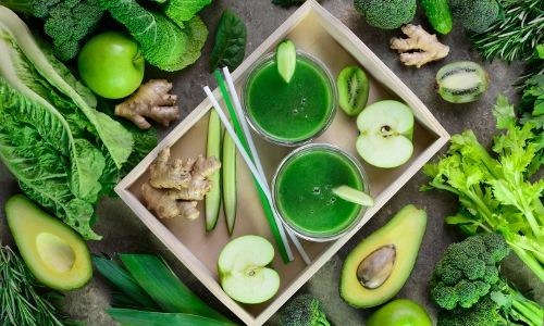 grünes Obst und Gemüse liegen auf einem Holztablett