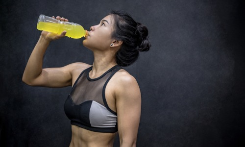 Frau in Sportkleidung trinkt isotonisches Getränk