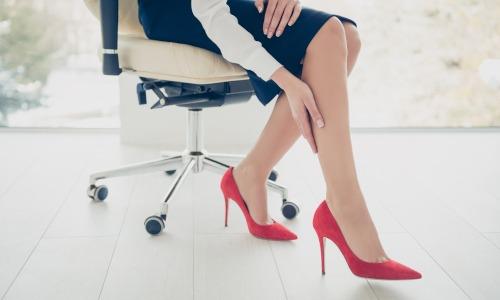 Frau auf Bürostohl und in roten High Heels massiert sich Waden wegen Wassereinlagerungen