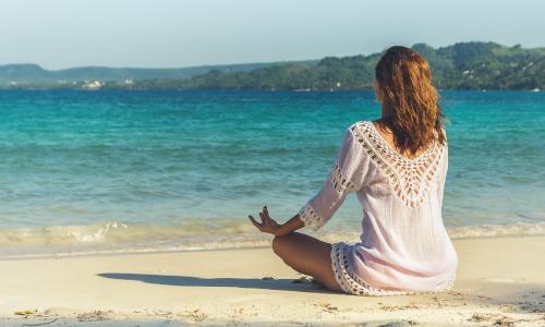 Frau mit weißer Bluse sitzt am Strand und macht Yoga Übungen