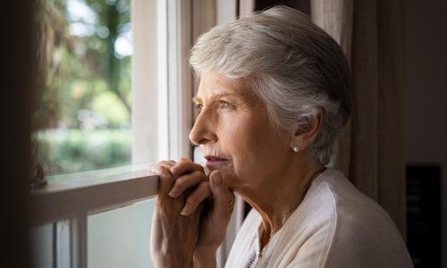 Frau mit Altersdepression schaut nachdenklich aus Fenster