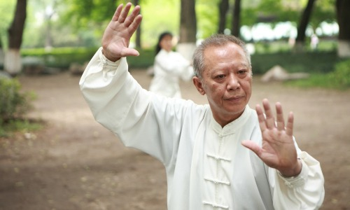 älterer chinesischer Mann weißer Anzug im Park macht Tai Chi Übung