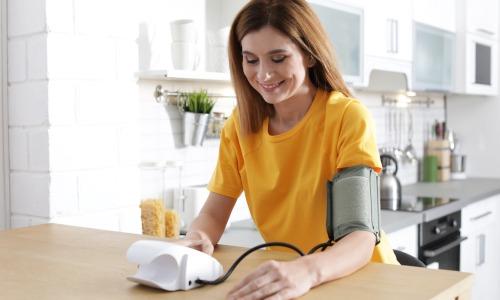 Junge Frau beim Blutdruck messen mit Blutdruckmessgerät