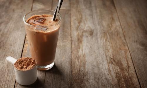 Scoop mit Proteinpulver gefüllt, Glas mit angerührtem Protein Shake, Holztisch
