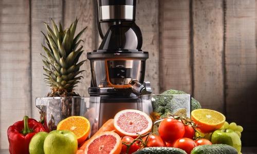 Slow Juicer mit einer Auswahl an unterschiedlichem Obst und Gemüse